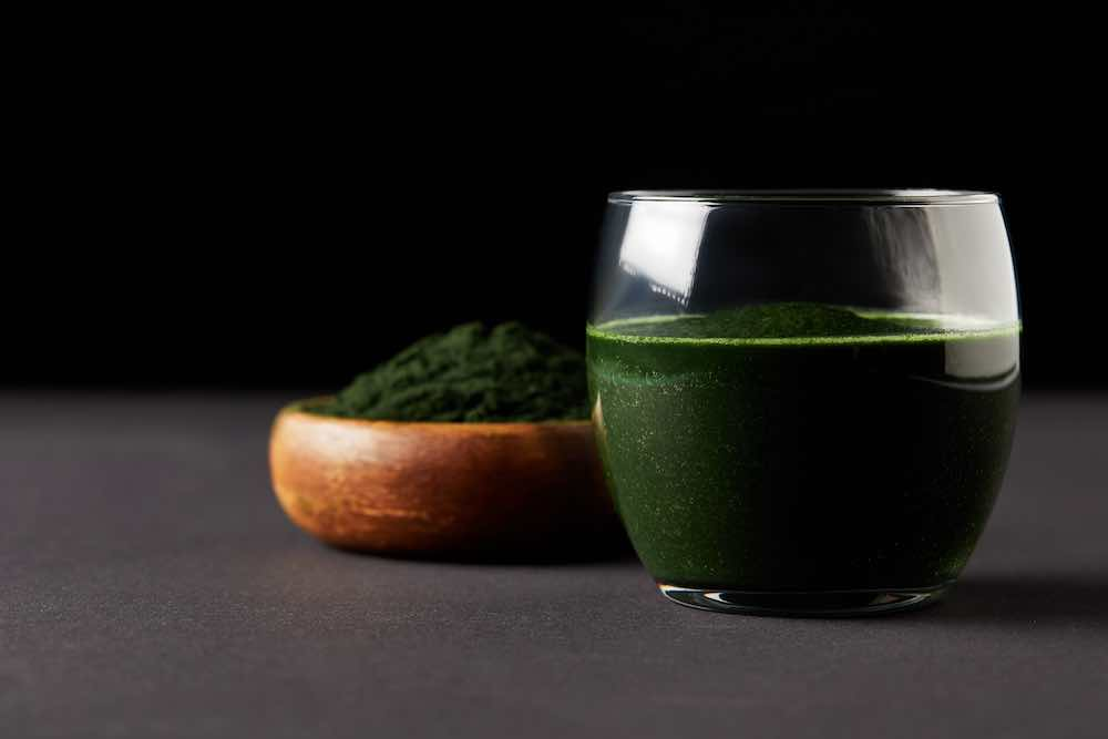 Glass of spirulina juice beside a bowl of powdered supplement