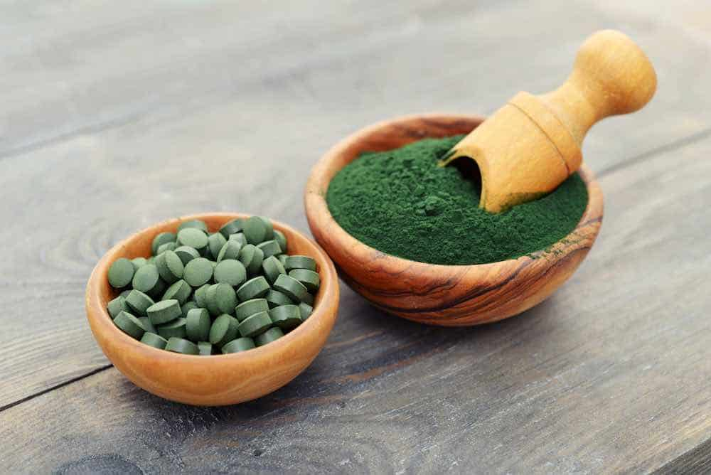 two bowls of spirulina: one full of powder, the other tablets