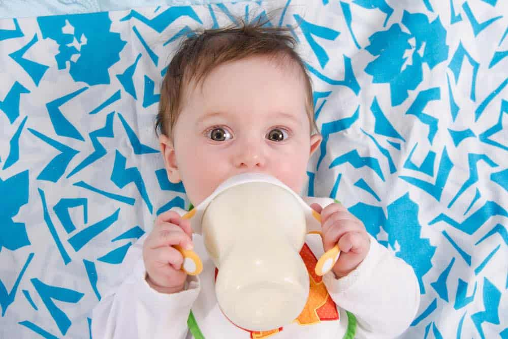 baby drinking soy milk formula on a colorful blanket