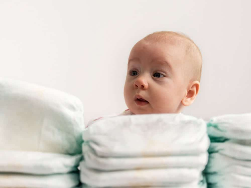 baby looking over a pile of the best disposable nappies