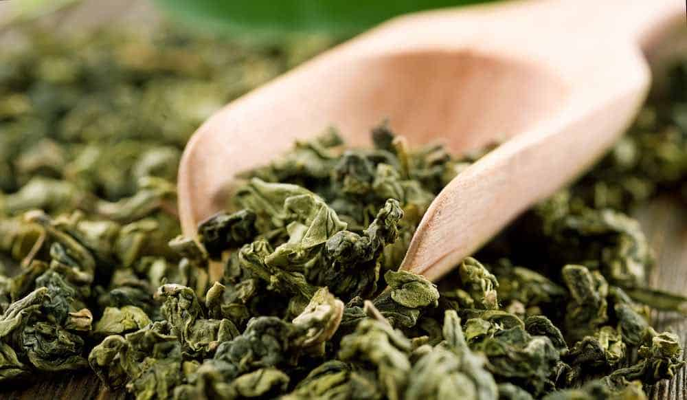 wooden scoop of dried loose leaves: history of green tea