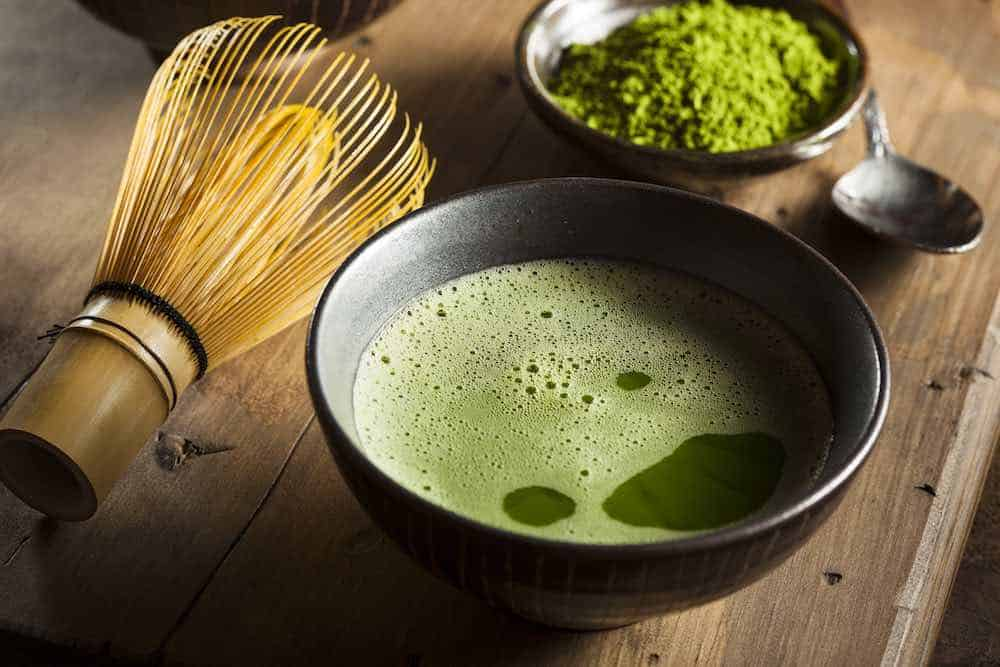 matcha green tea in a bowl with brewing brush