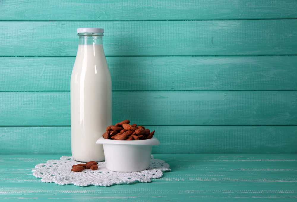 almond milk against a blue green wooden background
