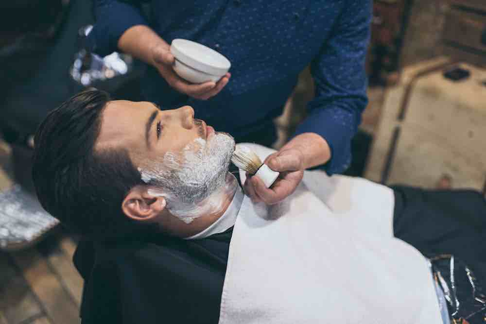 barber using shaving brush with synthetic bristles