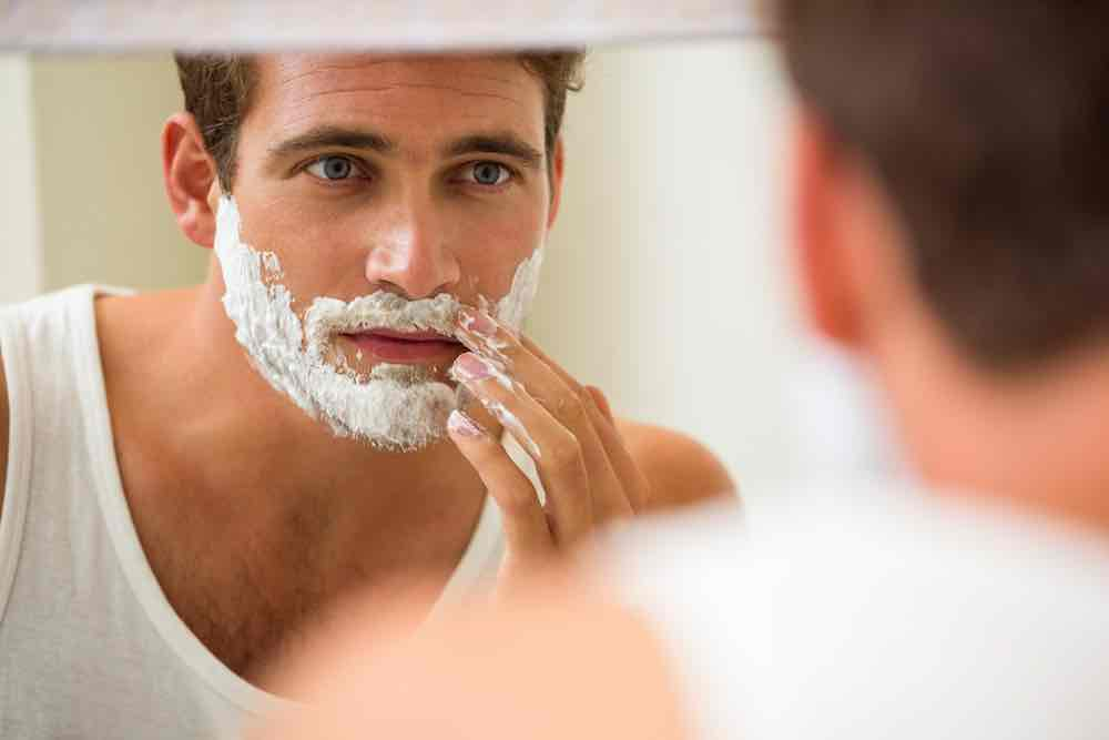 man applying vegan shaving soap