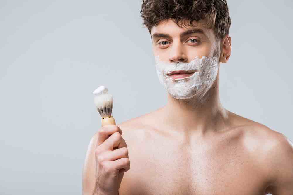 man holding synthetic shaving brush