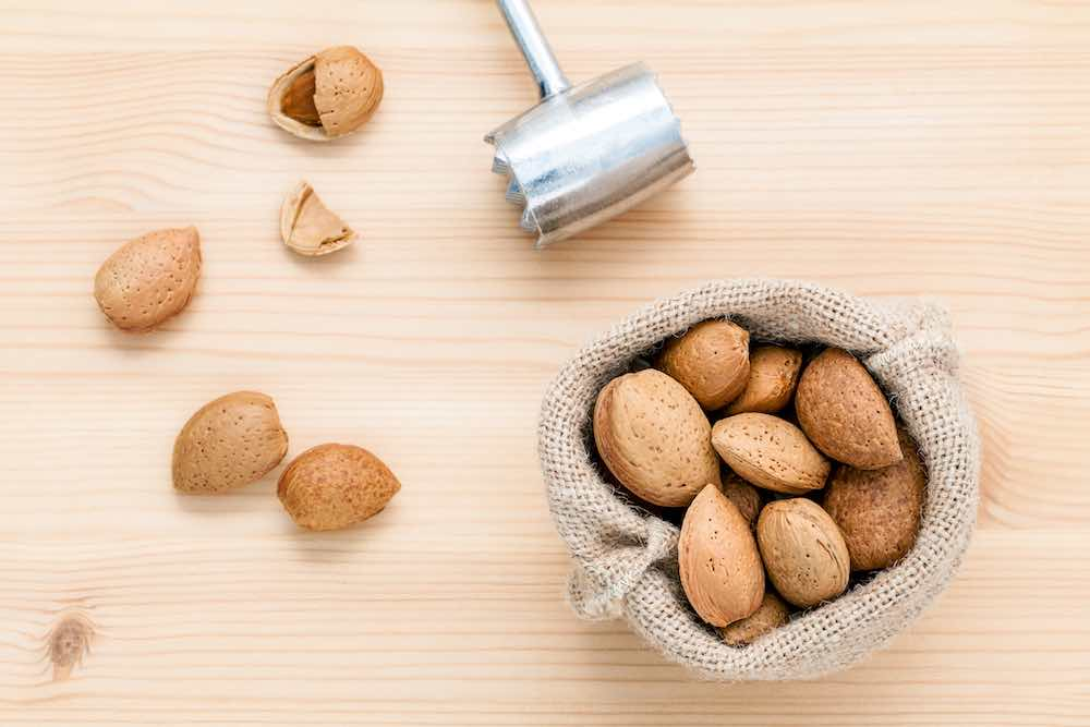 almonds in a bag next to a nut hammer