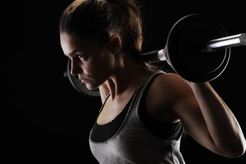 woman with barbell takes best bcaa powder for vegans