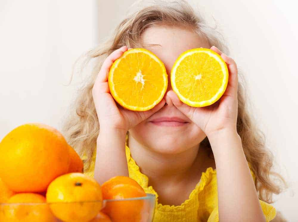 girl holding up two halves of an orange, using them for eyes